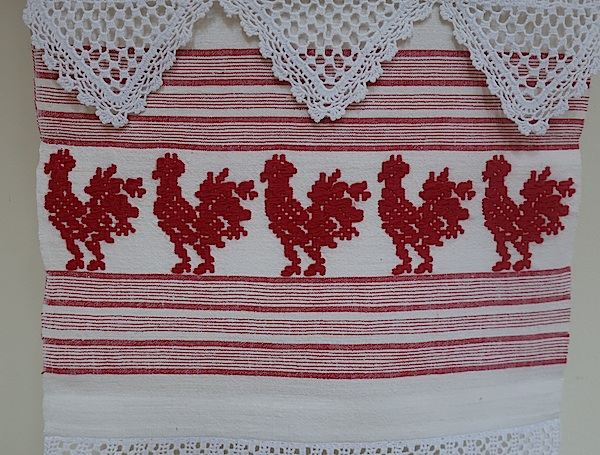 Motiv s ručnika: pevčeki u crvenom pismu na bijelom lanu / Fotografija Miljenko Brezak